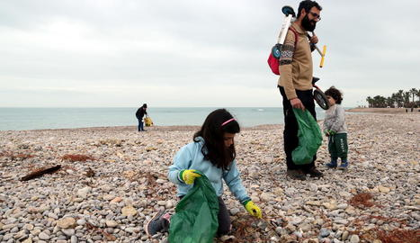 Famílies van netejar ahir les platges de les Cases d'Alcanar, plenes de brossa i plàstics pel pas del Glòria.