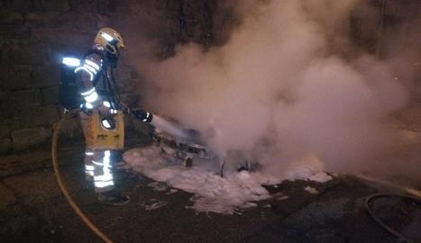 Un bomber apaga les flames al carrer Raval de Sant Francesc.