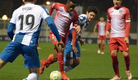 Cano condueix la pilota davant l'oposició de dos jugadors de l'Espanyol B.