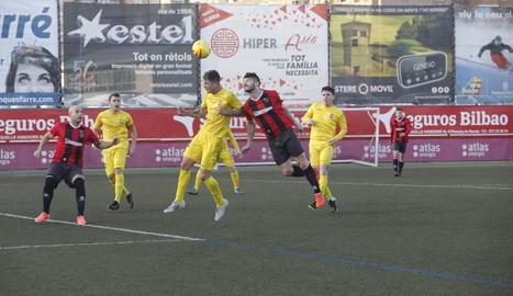 Pau Bosch disputa una pilota aèria amb un futbolista del Vilanova.