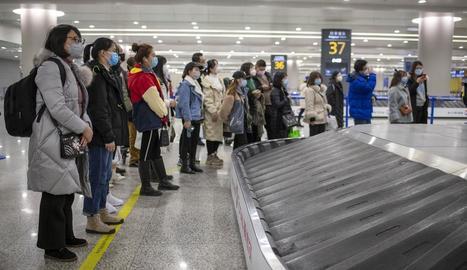 Passatgers (amb màscara) esperen per recollir l'equipatge a l'aeroport de Xangai.