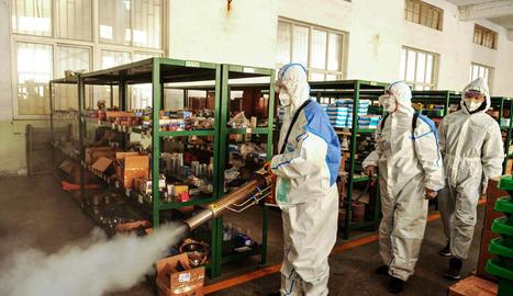 Voluntaris desinfecten una àrea administrativa davant del brot del coronavirus a Shandong, Xina.