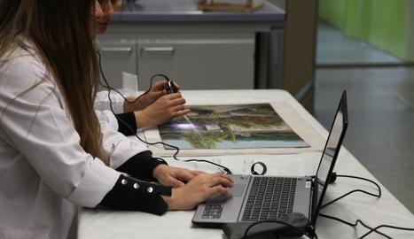 Dos investigadores del CAEM, Mariona Navarro i Jessica Martí, examinen la textura de la pintura.