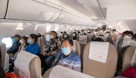 Passatgers d'un vol regional xinès, tots amb màscares.
