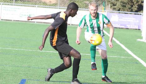 Un jugador de l'Alguaire intenta controlar la pilota davant d'un defensa del Pinyana.