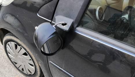Imatge d'un dels vidres trencats de la pista de pàdel i del retrovisor d'un cotxe arrancat.
