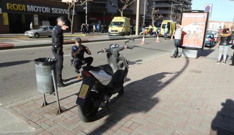 Imatge del ciclomotor que conduïa la víctima; al fons, els sanitaris atenen l'accidentat.