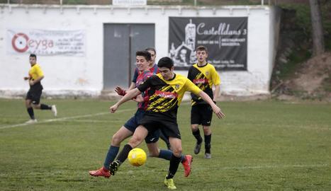 Un jugador visitant intenta controlar la pilota davant de la pressió dels rivals.
