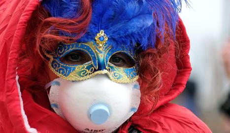 Una persona amb la màscara de Carnaval i una mascareta de paper pel coronavirus.