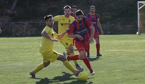 Un jugador del Vilanova de la Barca intenta controlar la pilota davant d'un defensa de l'Alcoletge.