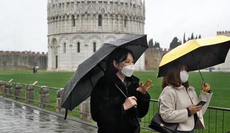 Turistes amb màscara passejant pels voltants de la torre de Pisa.