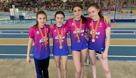 Maria March, Aran Badia, Èrika Sellart i Núria Argelich, amb les medalles. A la dreta, Daniel Cogul, campió en llançament de pes.