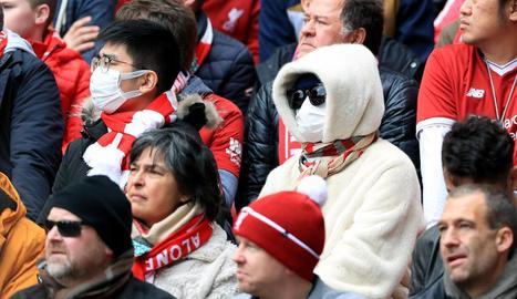 Aficionats veient ahir el Liverpool-Bournemouth amb màscares per por del coronavirus.