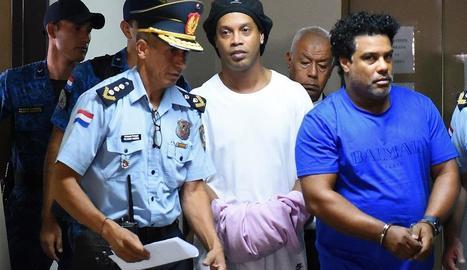 Ronaldinho oculta que està emmanillat amb un jersei a les mans.