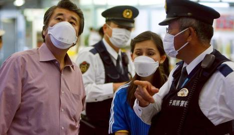 Ciutadans i policies japonesos utilitzen màscares per evitar contagiar-se.