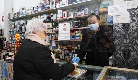 Un comerciant atén amb màscara i darrere d'una mampara.