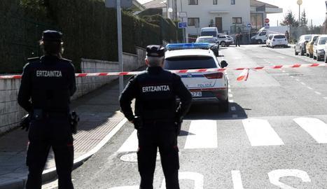 Dos agents de l'Ertzaintza a la zona acordonada al costat de l'habitatge on van trobar els cossos.