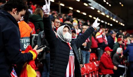 Un aficionat de l'Atlètic, amb màscara i guants, celebra la classificació de l'equip a Anfield.