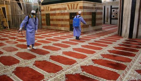 Treballadors palestins desinfecten una mesquita a la ciutat d'Hebron.