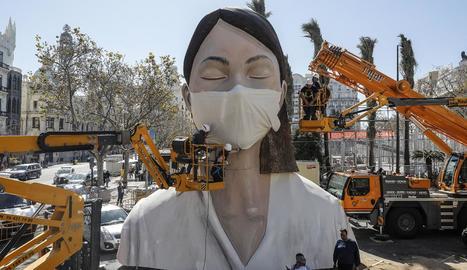 Posen una màscara a una figura després d'ajornar les Falles.