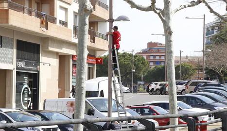 Un operari al despenjar ahir a Mollerussa els cartells que anunciaven la Fira de Sant Josep.