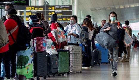 Diversos viatgers a l'aeroport de Barcelona, molts d'ells amb màscares.