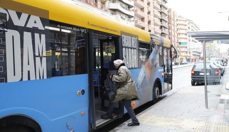 Una dona puja a un autobús per la porta posterior, ahir.