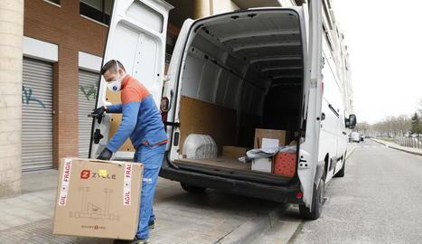 Un repartidor amb màscara i guants entregant un paquet a Lleida.
