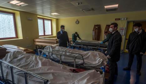 Treballadors ficant els morts en fèretres a Bèrgam.