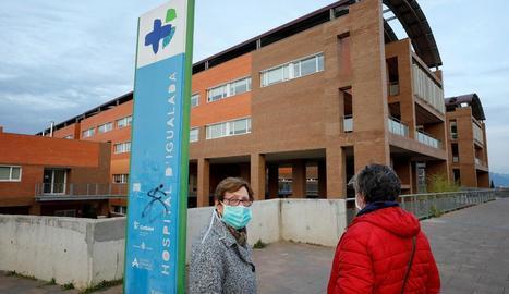 Dos dones amb mascareta davant de l'hospital d'Igualada.