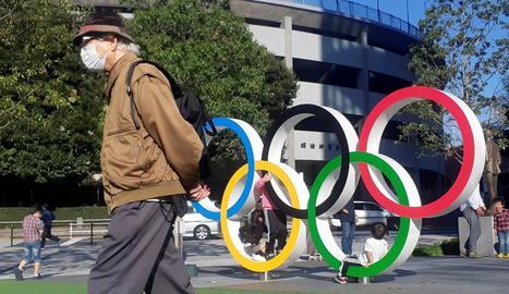 Un home protegit per una màscara passa pel costat dels anells olímpics instal·lats a Tòquio.