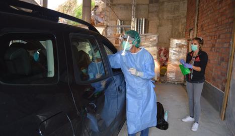 Professionals sanitaris recollint les mostres de les proves que detecten la covid-19 d'un pacient que les porta sense baixar del seu cotxe, en un espai adjacent a l'hospital andorrà.