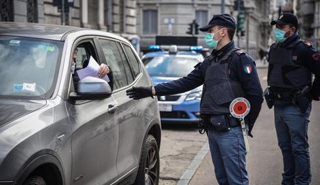 Control de la policia italiana a un vehicle, ahir. Els agents, amb mascareta, guarden les distàncies.