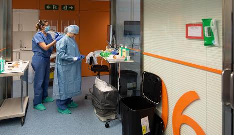 Una professional sanitària es protegeix abans d'entrar en una habitació d'un positiu per coronavirus a l'Hospital Clínic