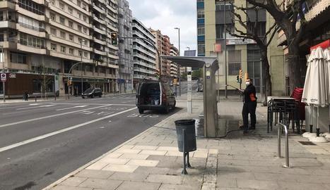 Un operari netejant una parada d'autobús a l'avinguda Catalunya, ahir al migdia.