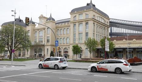 Dos taxis esperen clients a la parada habilitada davant l'estació de trens de Lleida.