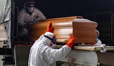 Soldats traslladen el fèretre d'una víctima del coronavirus a un cementiri pròxim a Milà, ahir.