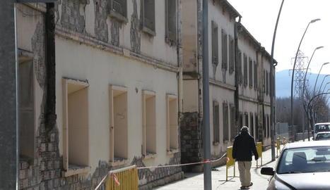 Un home al costat dels antics habitatges dels ferroviaris.