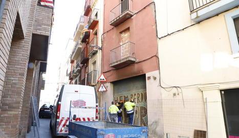 Operaris tornant a tapiar l'entrada a l'edifici calcinat.