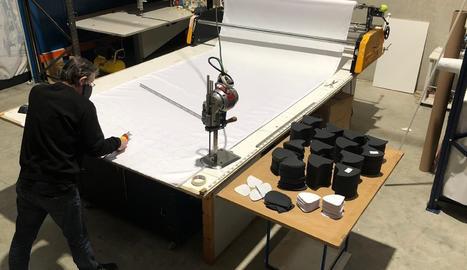 Un treballador de la companyia de Lleida, tallant peces per a l'elaboració de les mascaretes.