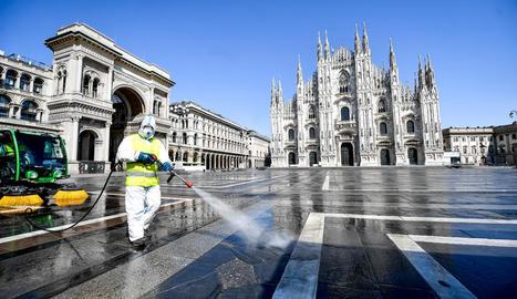 Un treballador italià efectua tasques de desinfecció del terra de la Piazza del Duomo de Milà.