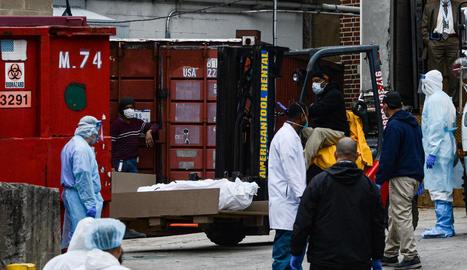 Operaris traslladen cadàvers de víctimes del coronavirus a una morgue provisional a Nova York.