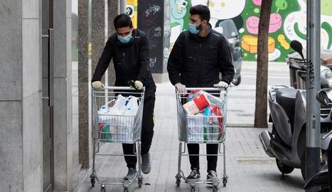 Dos treballadors d'un supermercat de Barcelona porten la compra a casa d'uns clients.