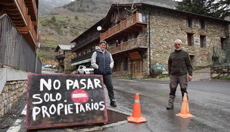 Veïns d'Os de Civís, a les Valls de Valira, amb els cartells que prohibeixen l'entrada als forans.