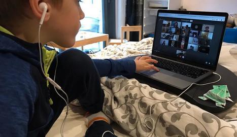 Un nen segueix una classe des de casa amb l'ordinador.