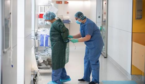 Una professional sanitària corda a una companya una bata abans d'atendre un pacient amb covid-19, en un dels blocs quirúrgics de l'Hospital Clínic de Barcelona habilitat com a UCI