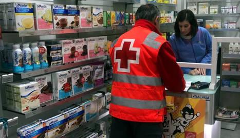 Un voluntari de Creu Roja recollint un medicament a una farmàcia de Lleida per portar-lo a un malalt.