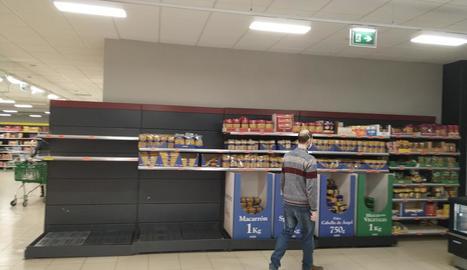 Ciutadans fan cua mantenint la distància de seguretat davant d'un supermercat al centre urbà.