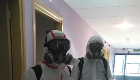 Dos treballadors desinfecten un dels centres de la Pobla.