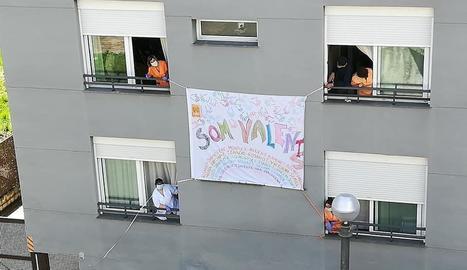 Els treballadors de la residència del Pont de Suert penjant una pancarta a la façana de l'edifici.